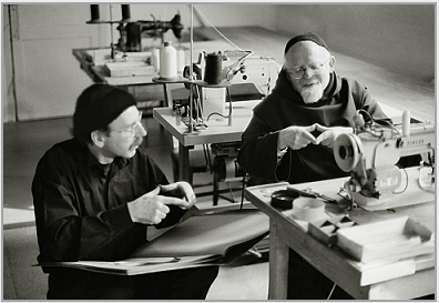 "Photograph of Père Robert, the tailor, (right), teaching Stanley Roseman Cistercian sign language in the tailor shop at the Abbey of La Trappe, 1998. The Trappist monk is showing the artist the sign for the word ""bread."" Photo © Ronald Davis"